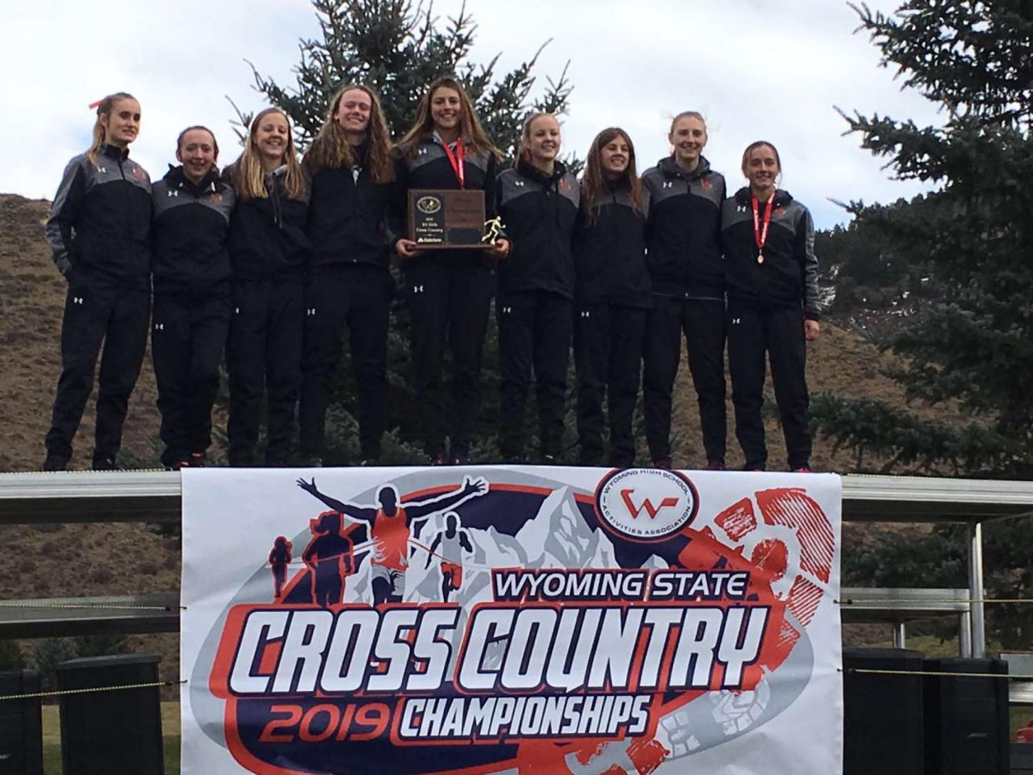Receiving the state champion plaque: The NC girls cross country state team stands on top of the podium at the Wyoming High school cross country state meet. This win makes the team two two time state champions.