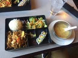 This lunch special has red curry , miso soup, salad, california rolls, and rice.